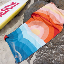 Load image into Gallery viewer, The Summer Chaser travel towel in Dipping Sun design in action on the beach.