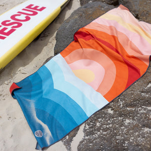 The Summer Chaser travel towel in Dipping Sun design in action on the beach.