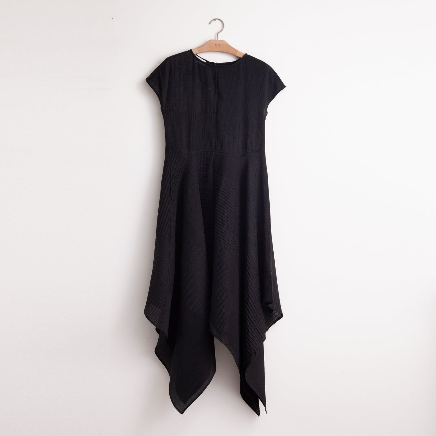 CO - Shortsleeve round neck dress with asymmetrical hem and set in waist in black lightweight textured crepe