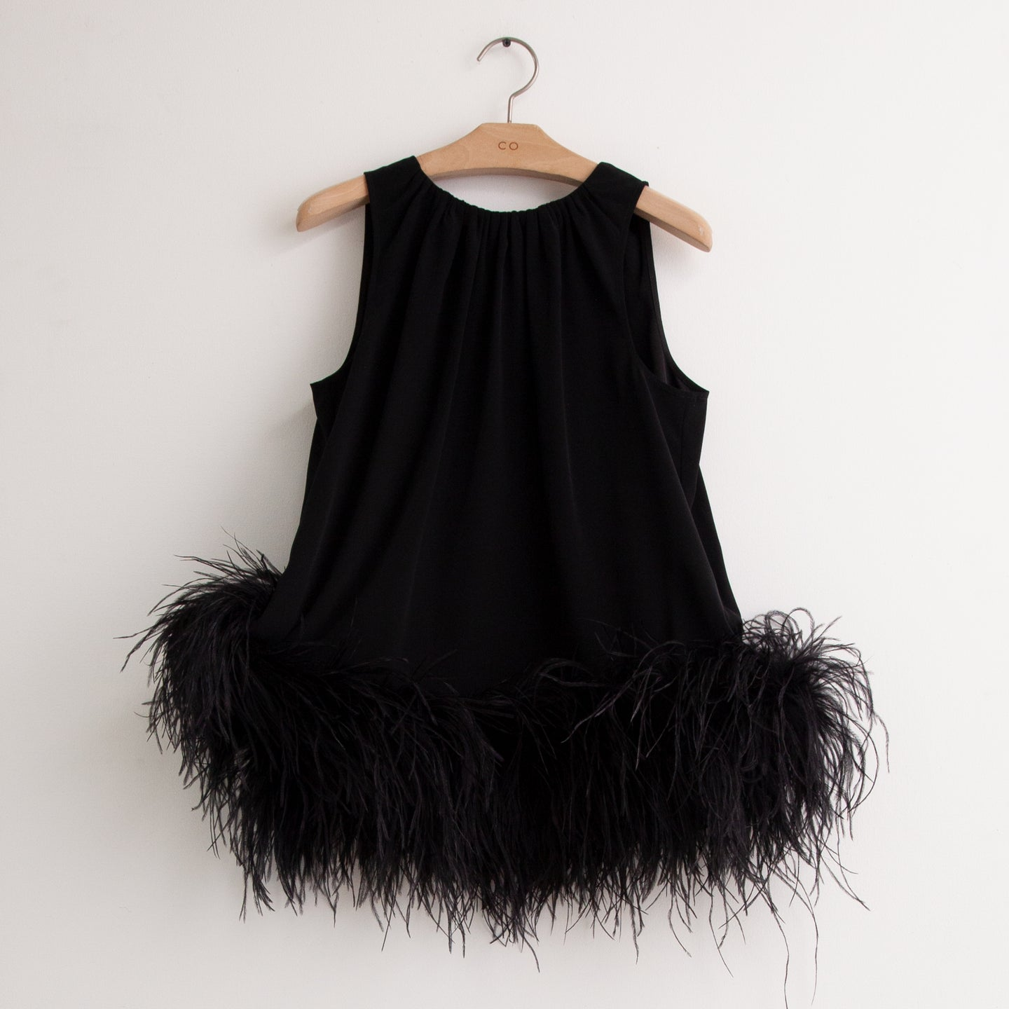 CO - Sleeveless top with feather hem detail and tie back in black stretch crepe.