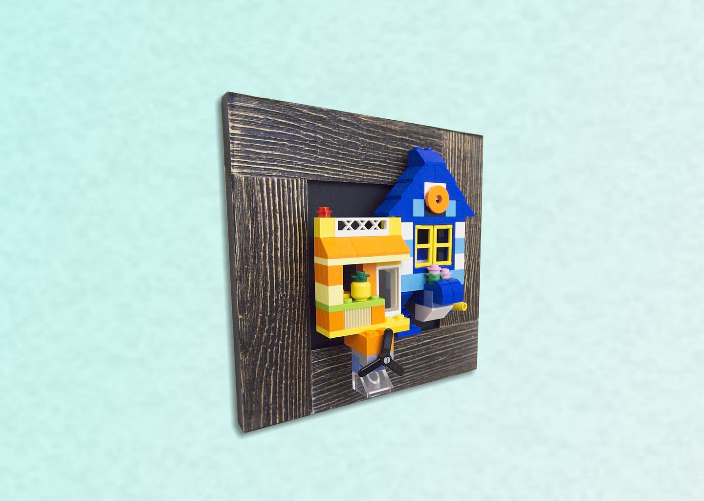 A blue and yellow flying home made from LEGO ® blocks is displayed on the wall using MBRIKS magnetic construction blocks.