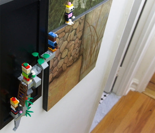 Characters made with LEGO ® blocks and supported by MBRIKS magnetic construction blocks climb onto a wall-mounted painting.