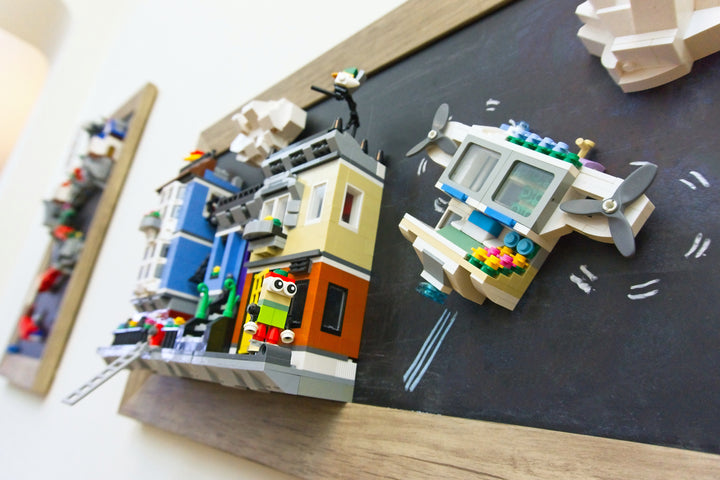 Buildings, a flying drone, and an onlooker created with MBRIKS magnetic construction blocks and LEGO ® blocks displayed on the wall on a magnetic chalkboard.