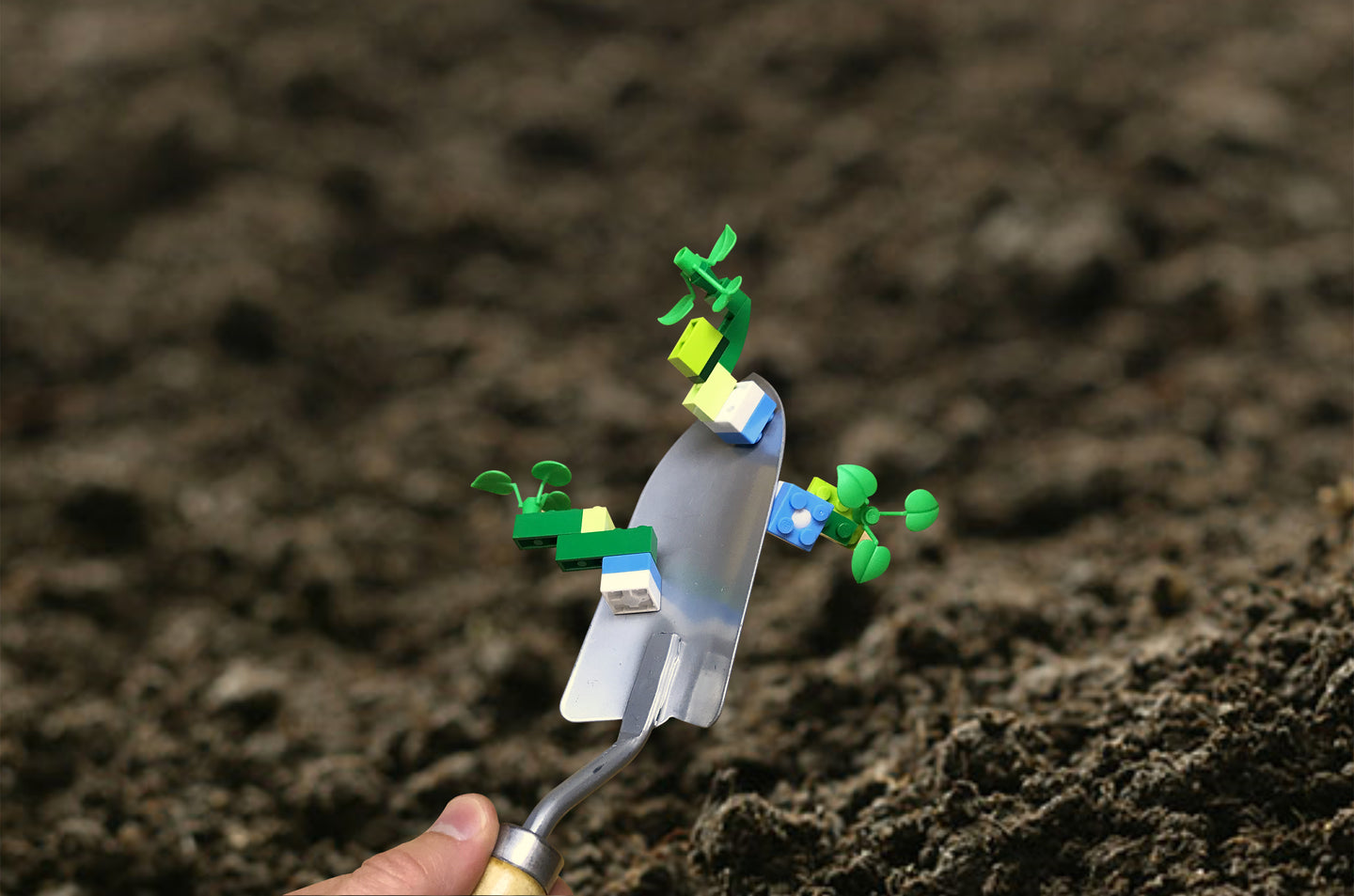 Three Mbrik plus LEGO creations are magnetically attached to a garden trowel.