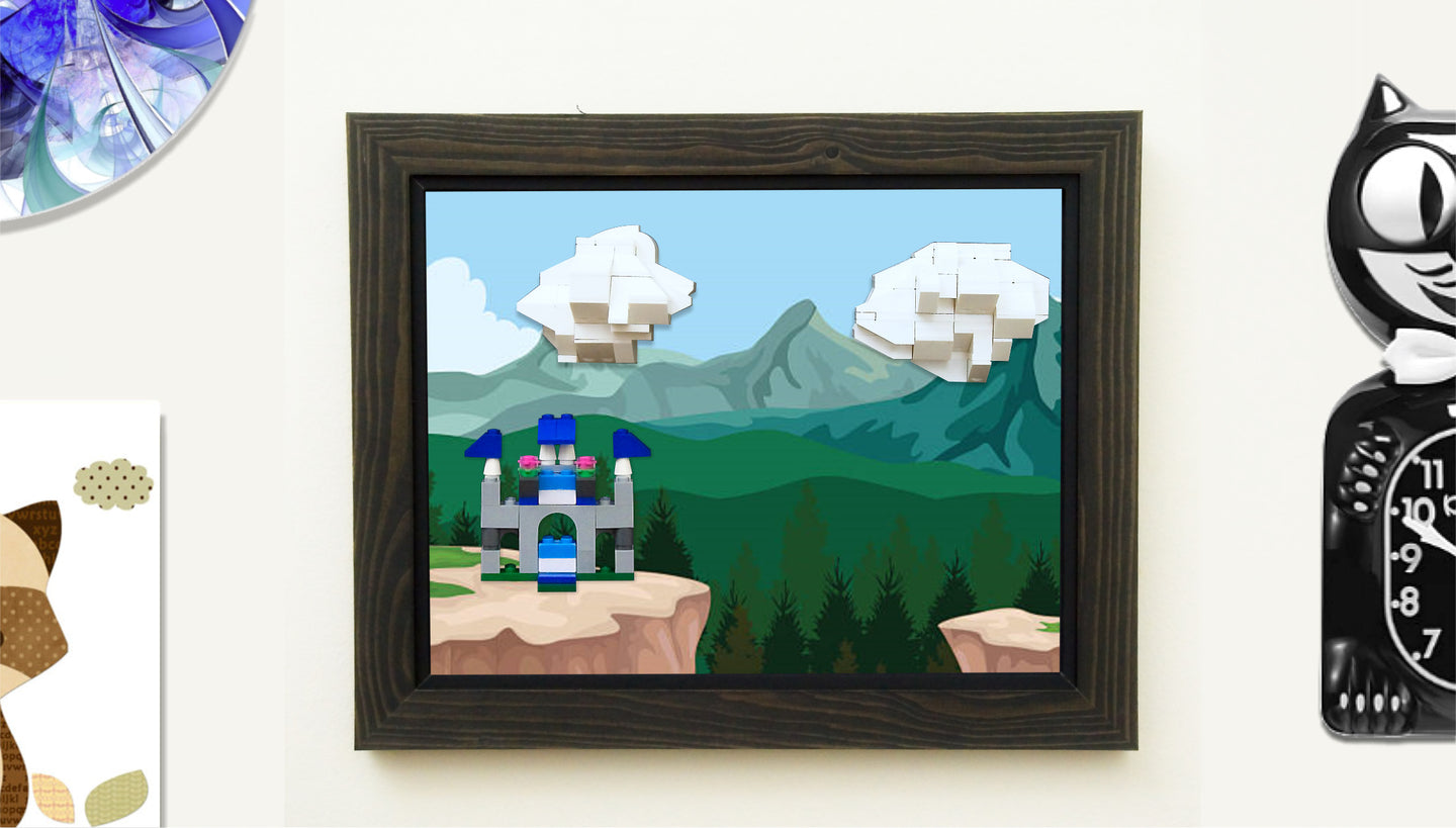 A castle and clouds made of LEGOs ® are attached to a wall-mounted frame by MBRIKS. The frame features a background image of a cliff and is positioned next to a cat clock and other wall mounted objects.