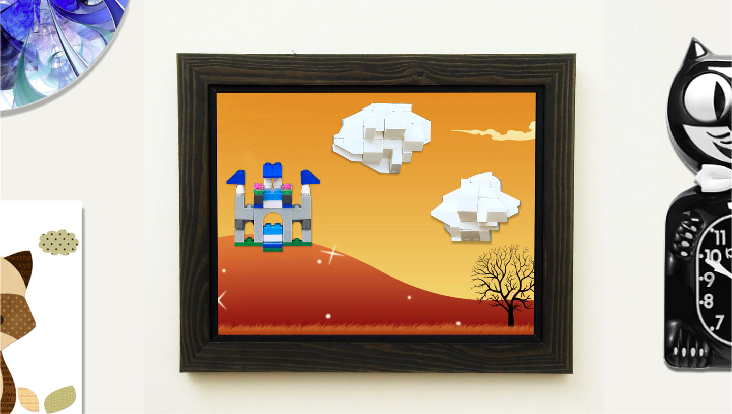 A castle and clouds made of LEGOs ® are attached to a wall-mounted frame by MBRIKS. The frame features a background image of a hill and tree and is positioned next to a cat clock and other wall mounted objects.