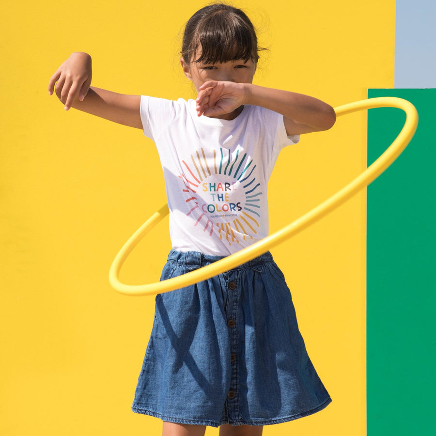 Girl hula-hooping wearing Pourquoi Princesse organic cotton white Share the Colors T-shirt.