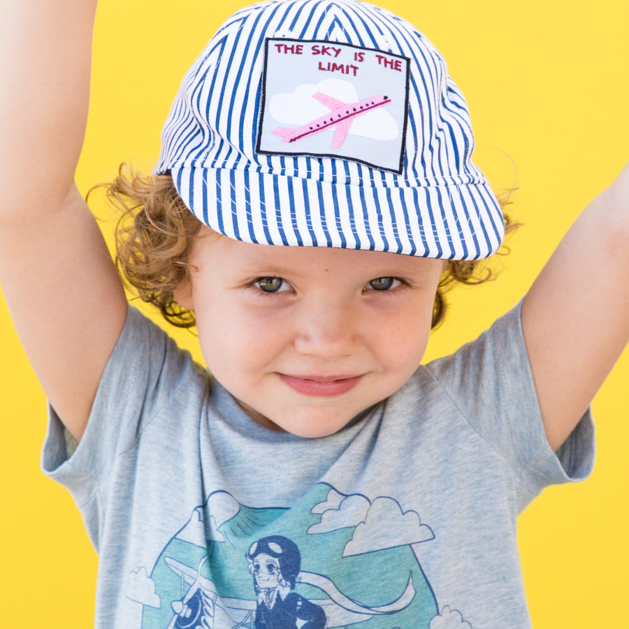 Little girl wearing baseball cap with Pouquoi Princesse iron on