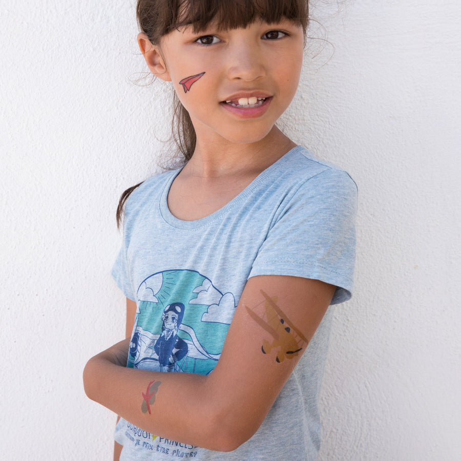 Girl wearing Pourquoi Princesse temporary Pilot tattoos.