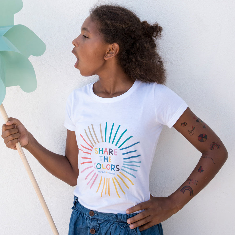 Girl wearing Pourquoi Princesse white organic cotton Share the Colors t-shirt and tattoos.
