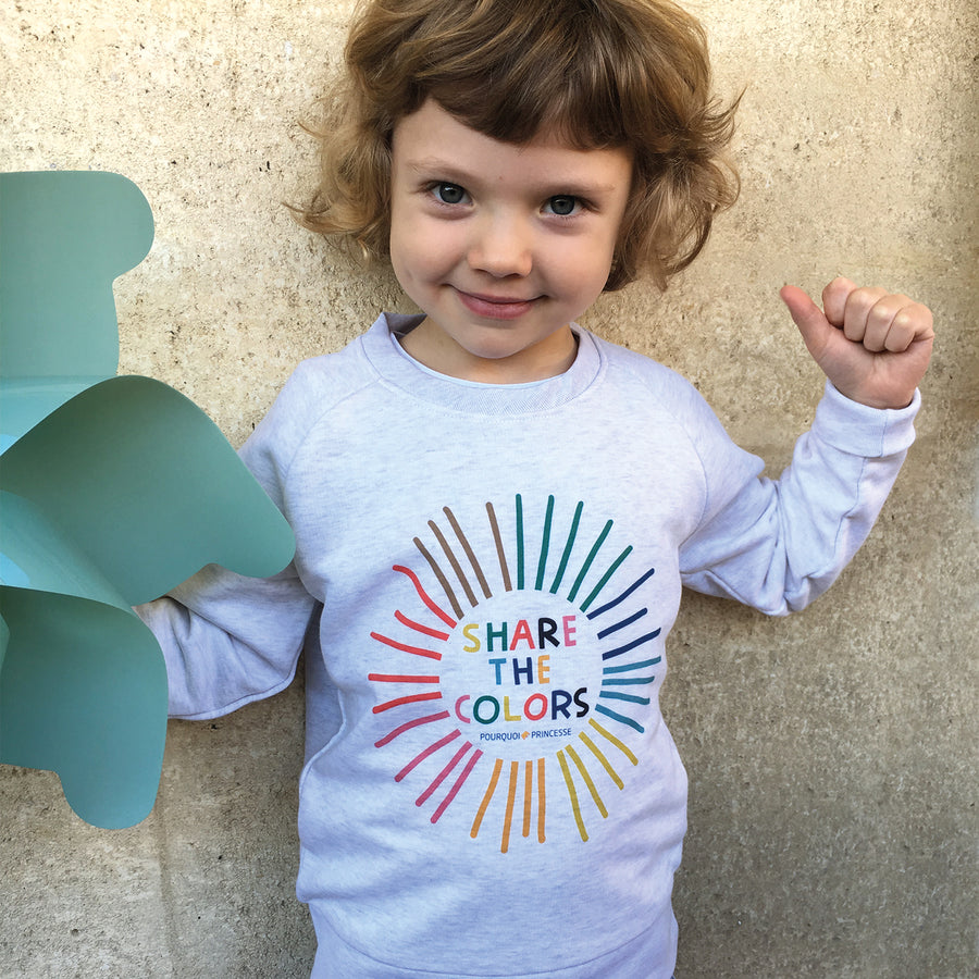 Girl wearing Pourquoi Princesse white organic cotton Share the Colors raglan sweatshirt.