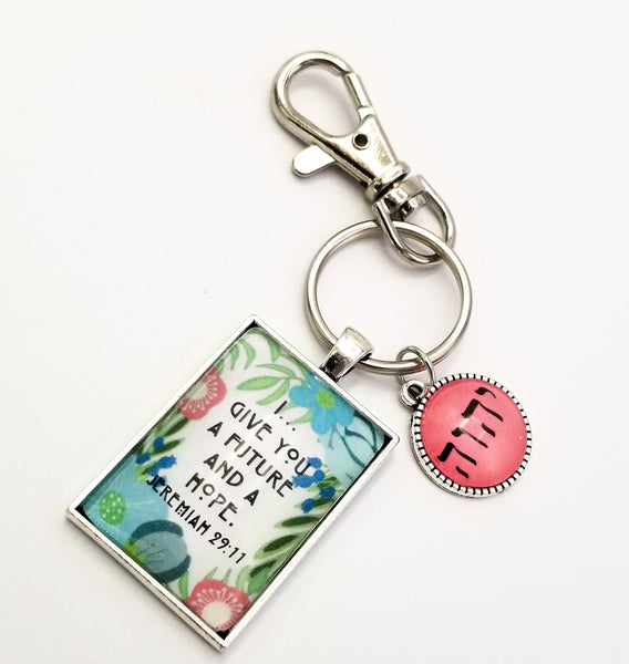 "This picture features a keyring that says ""I... Give You A Future and a Hope"" set against a floral background along with a Tetragrammaton charm."