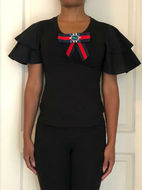 Black blouse with short ruffled puff sleeves and jeweled red/blue ribbon.