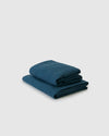 Side angle shot of dark adriatic blue flat and fitted sheet set