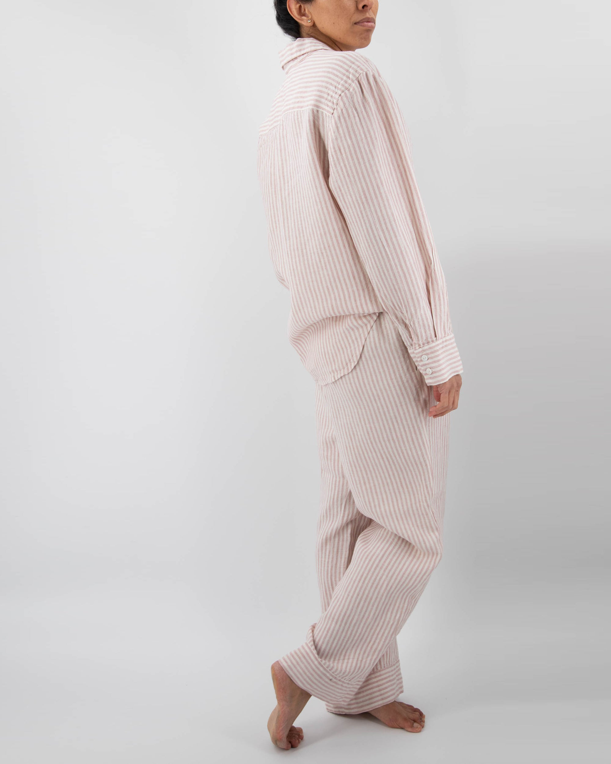 Model in pink linen striped pajamas (long sleeved shirt and long pants)