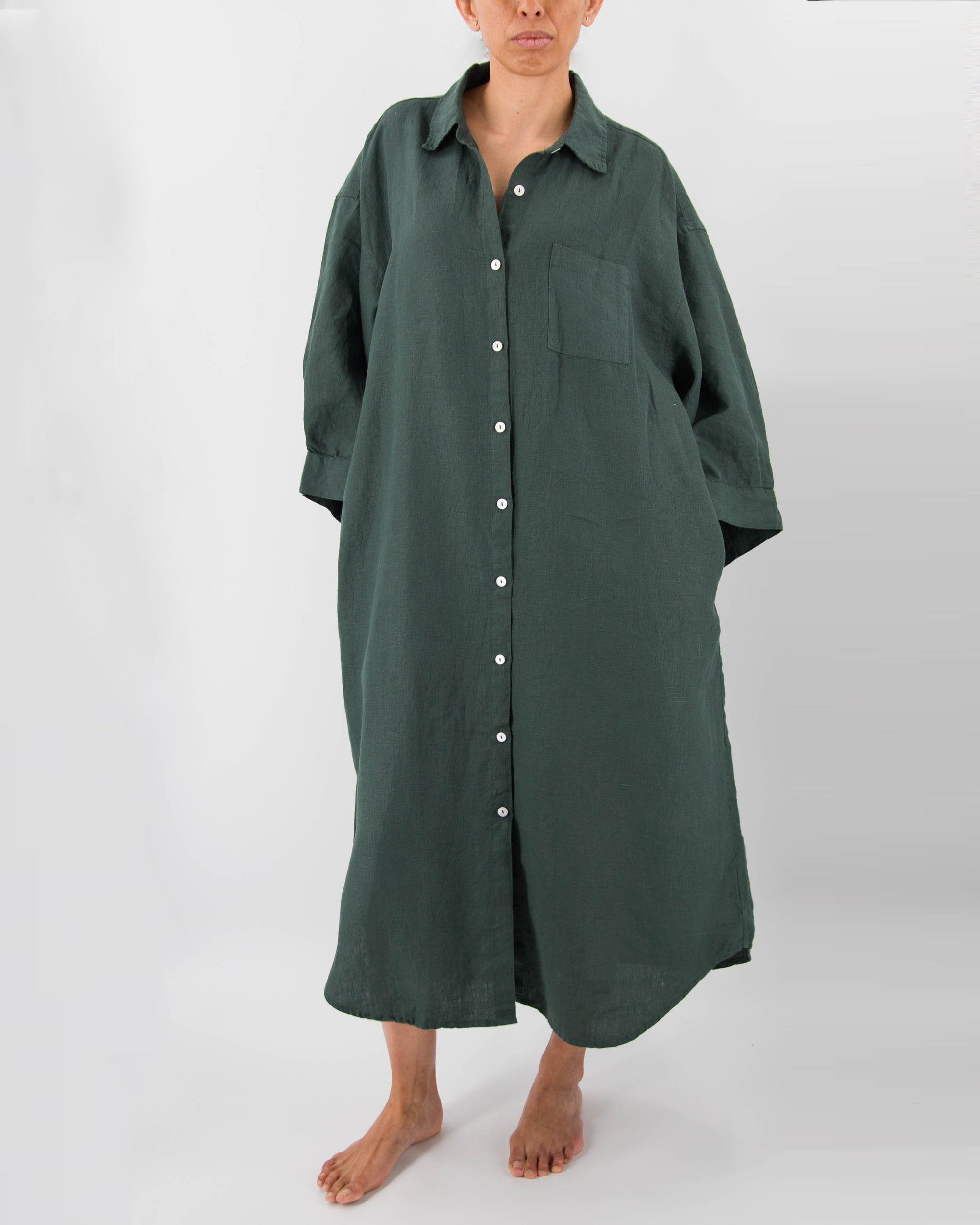 Side profile of model with full-length linen dress with buttons and front pocket in pine green