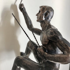 A antique bronze climbing man wall sculpture with twist wire cord and loop for easy hanging