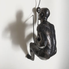 A antigiue bronze wall climbing man sculpture wall art hung on a twisted cord with loop top