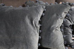 Grey cotton velvet cushion with pom poms