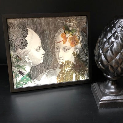 Femmes (two vintage women in black and white facing each other, with small accents of green and orange, Poster & Black Frame, 20 x 25 cm