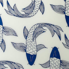 Round drinks tray with sketched koi fish in blue on a cream background