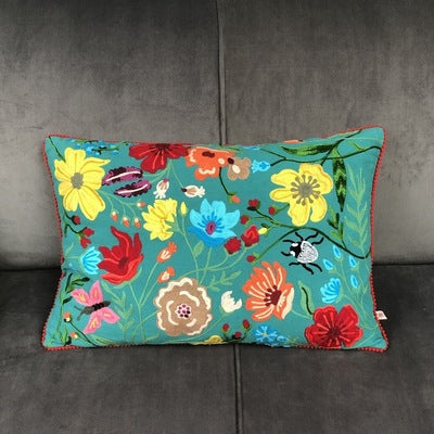 Green Floribunda Embroidered Wildlife Cushion. Hand embroidered with meadow of flora, fauna, bugs with red mini pom-pom edging, creates a striking and beautiful floral wildlife scene.