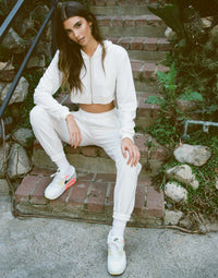 Summer Haus Crop hoodie jacket and jogger set in white; trimmed in rhinestone. Front view.