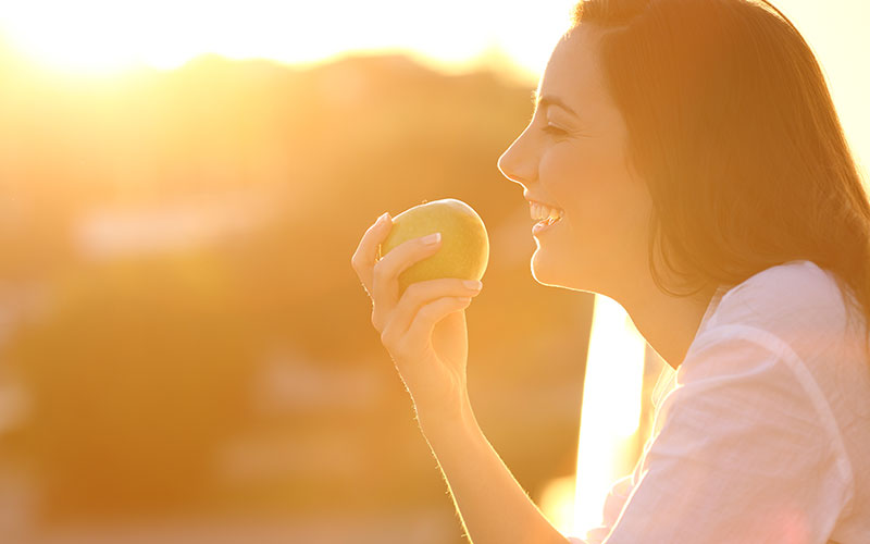 woman eating an apple at sunset