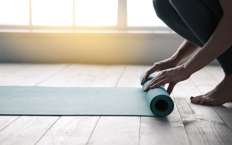 Woman rolling out yoga mat in the morning