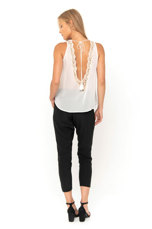 White sleeveless top with handmade embroidery details.