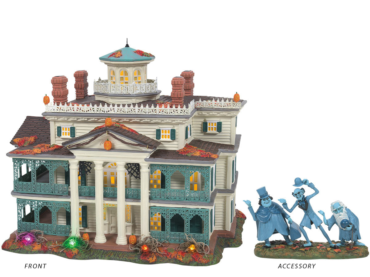 Disneyland Haunted Mansion lit building and Beware of Hitchhikers figurine