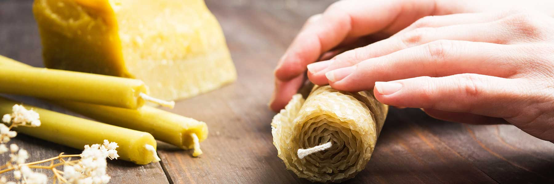 Close up of a pair of hands rolling a beeswax candle.
