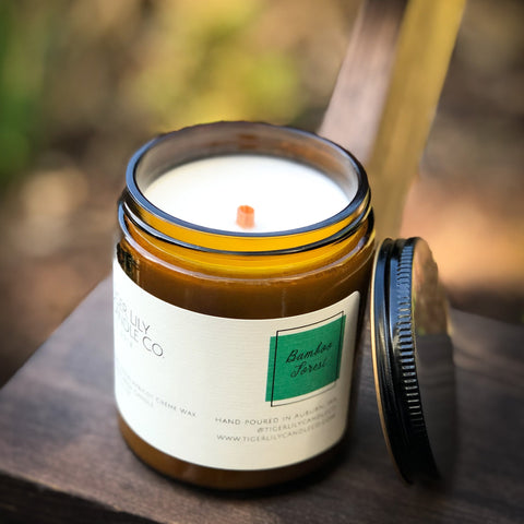 Outdoor photo of beautiful amber candle with wooden wick bamboo forest