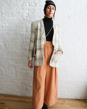 Persian model wearing a consignment brooklyn beanie in black. In a casual standing repose, wearing a small Dior copper crossbody, a black and white open front tweed Chanel jacket and peach corduroy high waisted Ulla Johnson wide leg pants.