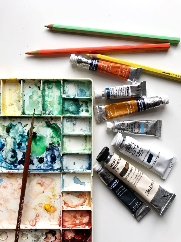 Watercolour paint tubes and pencils