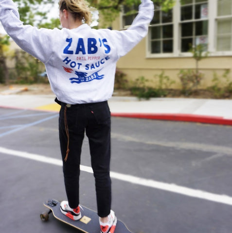 Made in Los Angeles, CA woman in skateboard with Zab's branded sweatshirt