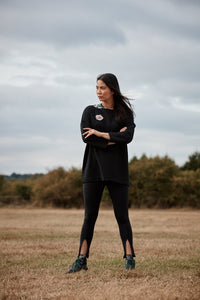 Woman wearing the Asmuss Twisted Legging with front zip detail. Use them for exercise or use them to layer up your own unique style.
