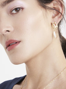 Model wearing gold leaf earrings with pearls in blue top