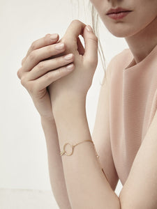 Model wearing peach top and gold chain bracelet with circle