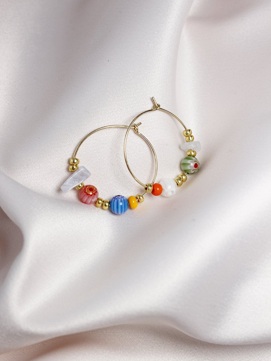 Gold hoops with colourful beads on a fabric background