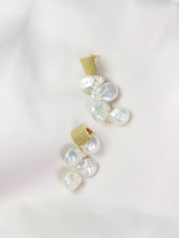 Pearl earrings cascading from a square gold stud