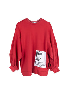 Red oversized organic cotton jumper with oversized pleated sleeves and sustainable patches. Made by ethical clothing brand Fanfare Label.