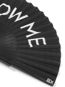 Close up of Khu Khu Blow Me Hand-Fan. White Font BLOW ME on black background with black wooden sticks and black rivet.