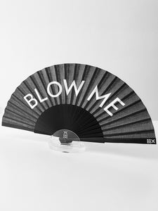 Khu Khu Blow Me Hand-Fan. White Font BLOW ME on black background with black wooden sticks and black rivet. Fan sits in acrylic table stand.