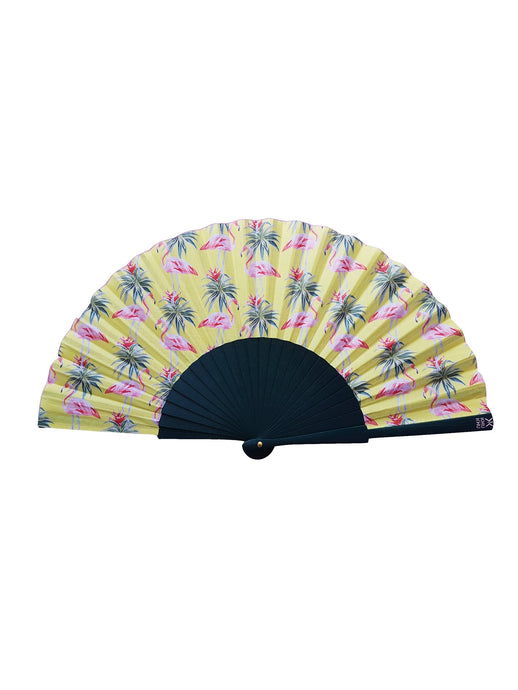Khu Khu flamingo hand-fan with pink flamingo with green leaves print on yellow background. Jungle green wooden sticks. Pink logo and fabric rim detailing.