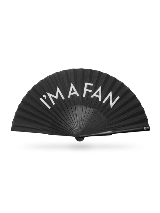 Khu Khu I'M A FAN hand-fan. White font on black cotton fabric with black painted wooden sticks. White logo on end of sticks and black detailing (rivets and fabric rim)