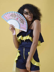 Model wearing blue and yellow matching shorts and holding Khu Khu Love Lynx fan with pink tassel.