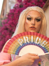Trans-gender model holds Khu Khu PRIDE SPARKLER hand-fan with sparkly font on rainbow background