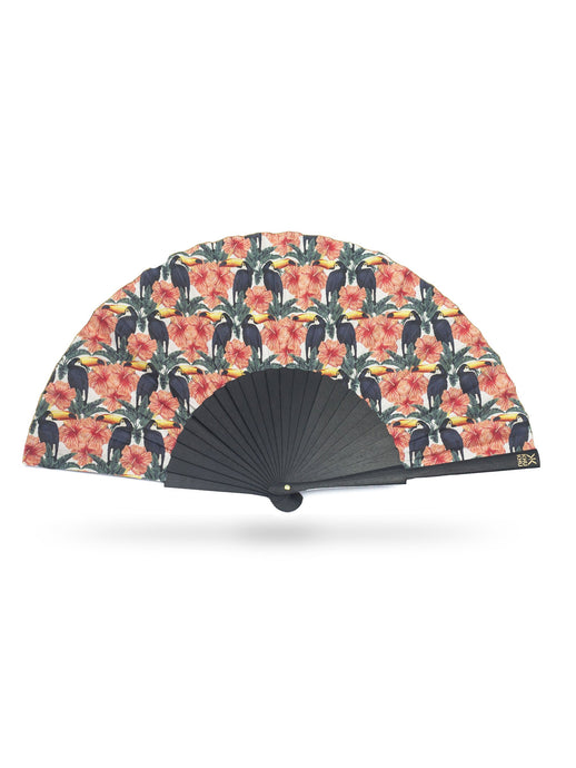 Khu Khu Toco Toucan Hand-Fan. Beak to beak toucans in a print with coral orange flowers and green leaves. Gold detailing..