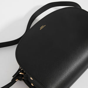 Top detail of APC Half Moon Saffiano Leather Crossbody in Black with logo detail and strap
